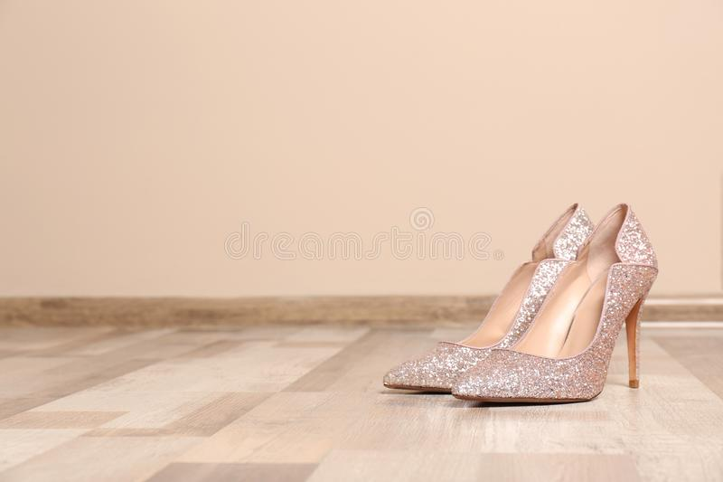 Paar hoog gehielde schoenen op vloer dichtbij kleurenmuur stock afbeeldingen
