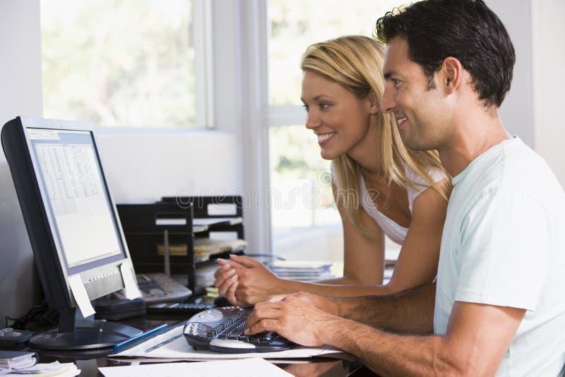 Paar in huisbureau dat computer en het glimlachen gebruikt