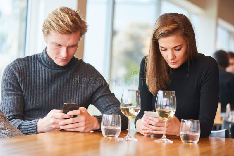 Paar ist mit Smartphone in der Hand still stockbilder