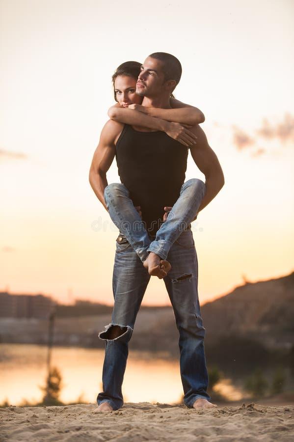 Paar in jeans op het strand stock afbeeldingen