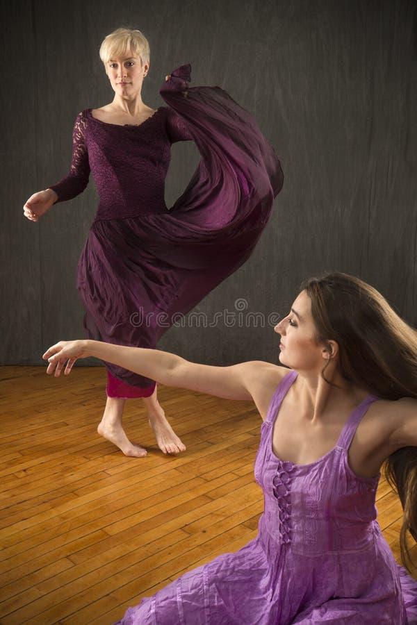 Paar jonge vrouwen in kleding die in de studio dansen stock foto's