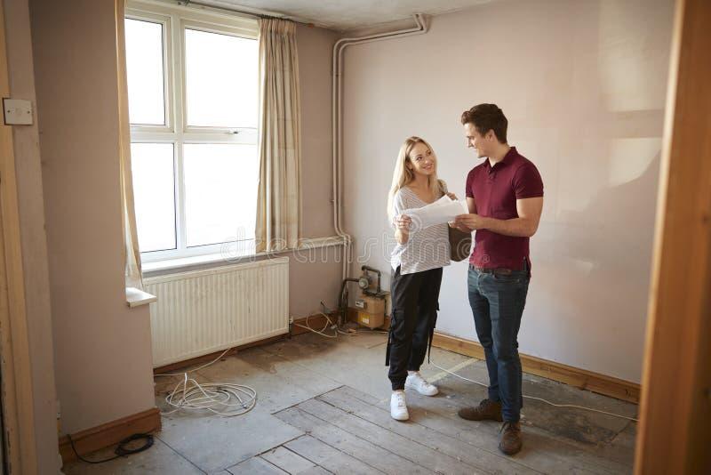 Paar-kaufendes Haus für das erste Mal, das Haus-Übersicht im Raum erneuert zu werden betrachtet lizenzfreie stockfotos