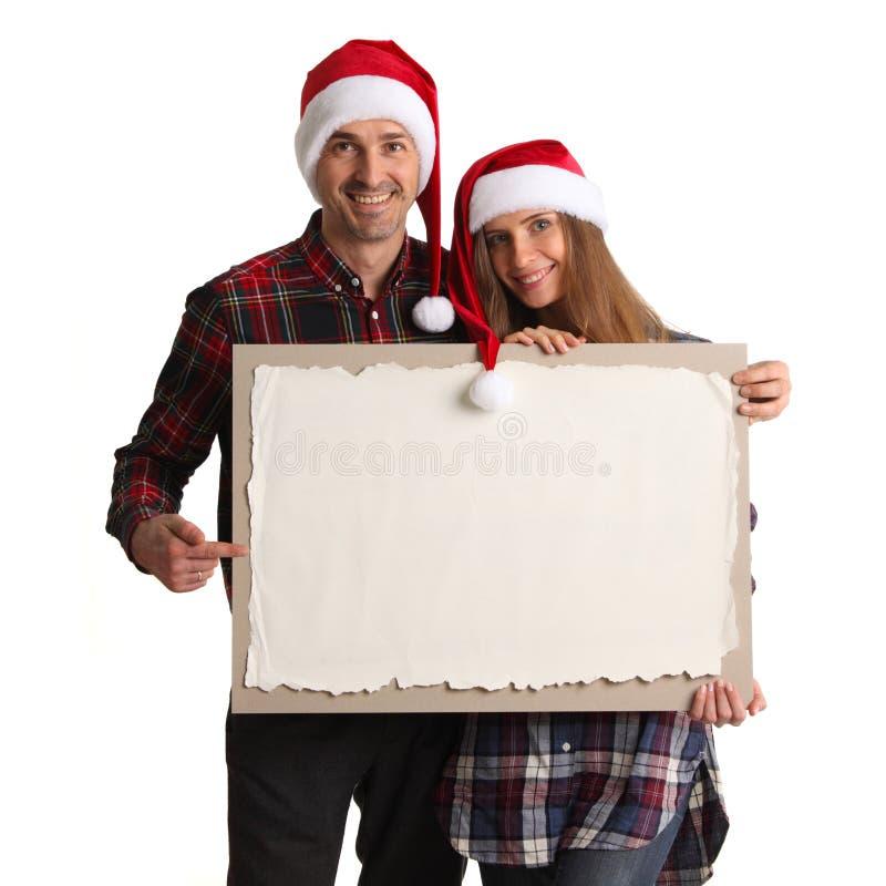 Paar in Kerstmanhoeden met banner stock afbeeldingen