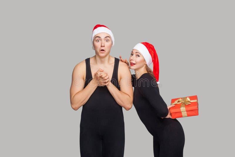 Paar in Kerstmishoed Geschokte mens die camera bekijken vrouw ho stock foto's