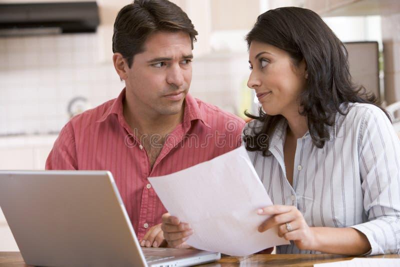 Paar in keuken met administratie die laptop met behulp van royalty-vrije stock foto's