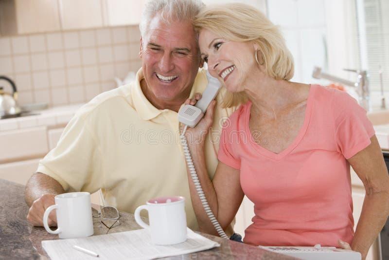 Paar in keuken met koffie die telefoon met behulp van stock fotografie