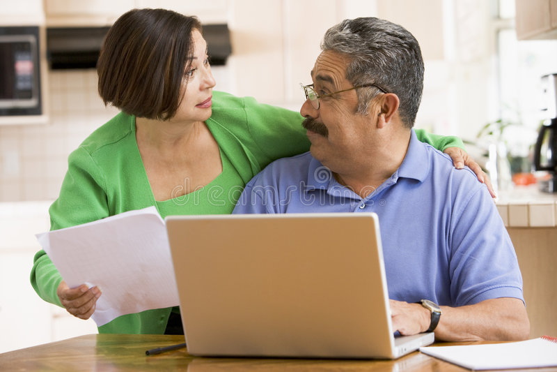 Paar in keuken met laptop en administratie stock foto