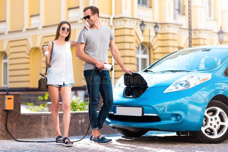 Paar klaar om op elektrisch voertuig te gaan stock afbeelding