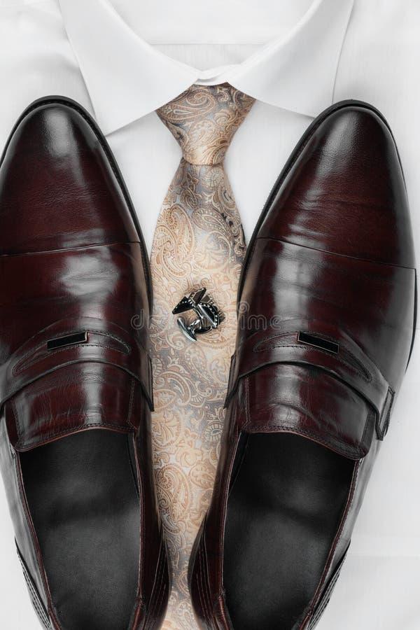 Paar klassieke bruine schoenen die zich op een overhemd en een band bevinden Mensen` s manier stock foto's