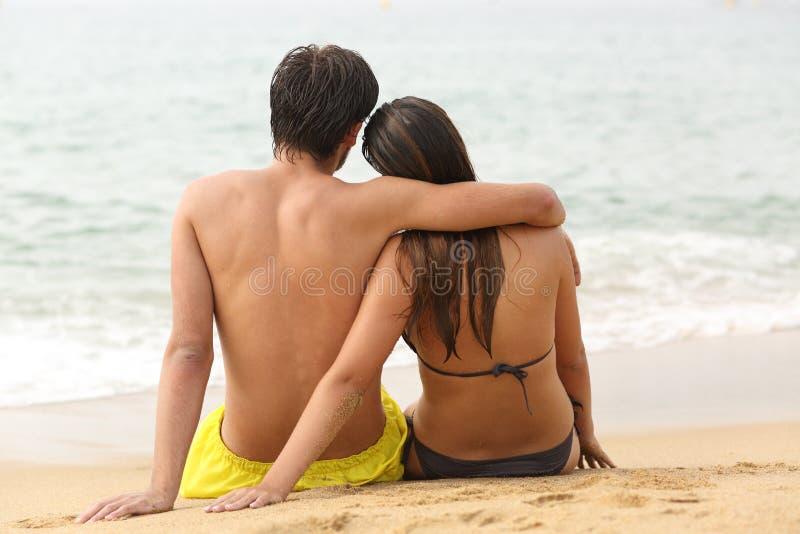 Paar koesteren die oceaan op het strand bekijken stock afbeelding