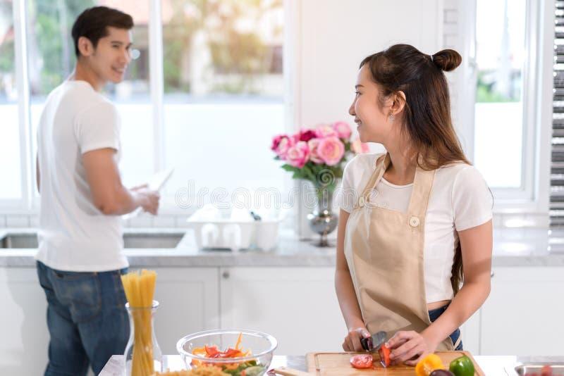 Paar kokend voedsel in keukenruimte, de Jonge Aziatische mens en vrouw samen stock fotografie