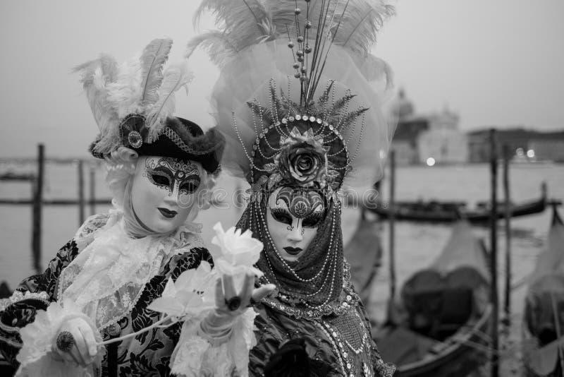 Paar in kostuum en maskers die zich met terug naar Grand Canal, San Giorgio op de achtergrond, tijdens Venetië Carnaval bevinden stock foto's