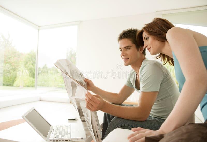 Paar-Lesezeitung zu Hause stockbild