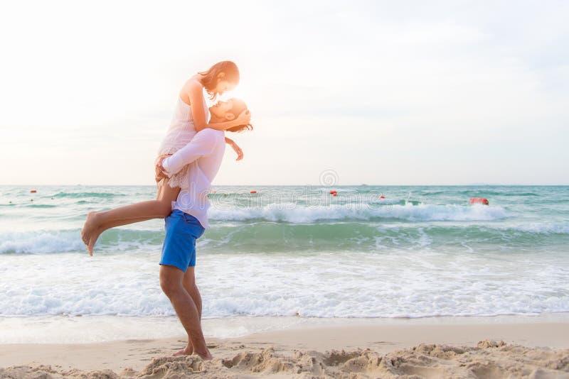Paar in liefde De glimlachende Aziatische jonge mens houdt meisje in zijn wapens op het strand op avondtijd stock afbeeldingen