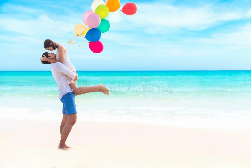 Paar in liefde De glimlachende Aziatische jonge mens houdt meisje in zijn wapens op het strand met multikleurenballon, royalty-vrije stock afbeeldingen