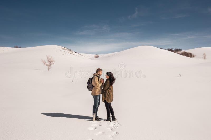 Paar in liefde in de winter in de bergen die hete thee drinken stock afbeelding