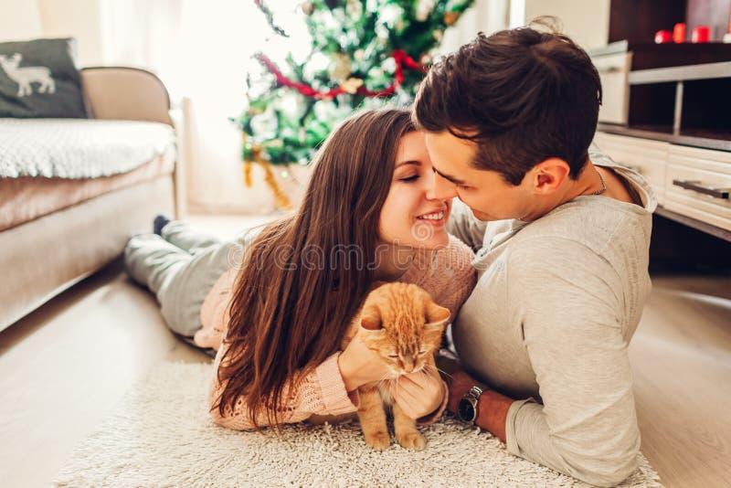 Paar in liefde die door Kerstboom liggen en met kat thuis spelen Het kussen van de man en van de vrouw royalty-vrije stock afbeelding