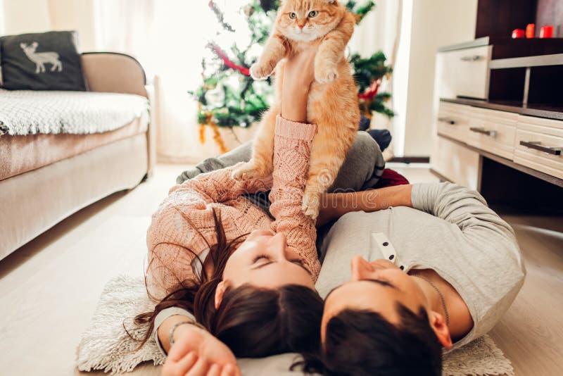 Paar in liefde die door Kerstboom liggen en met kat thuis spelen Man en vrouwen het opheffen huisdier in handen stock foto's