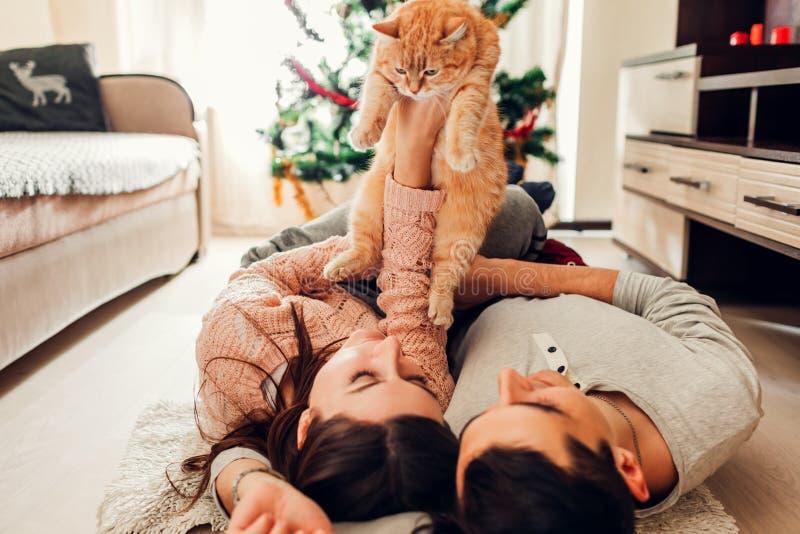 Paar in liefde die door Kerstboom liggen en met kat thuis spelen Man en vrouwen het opheffen huisdier in handen royalty-vrije stock afbeelding