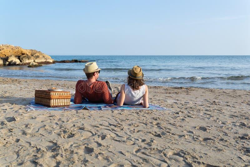 Paar in liefde die een picknick op een mediterraan strand hebben bij zonsondergang stock foto's