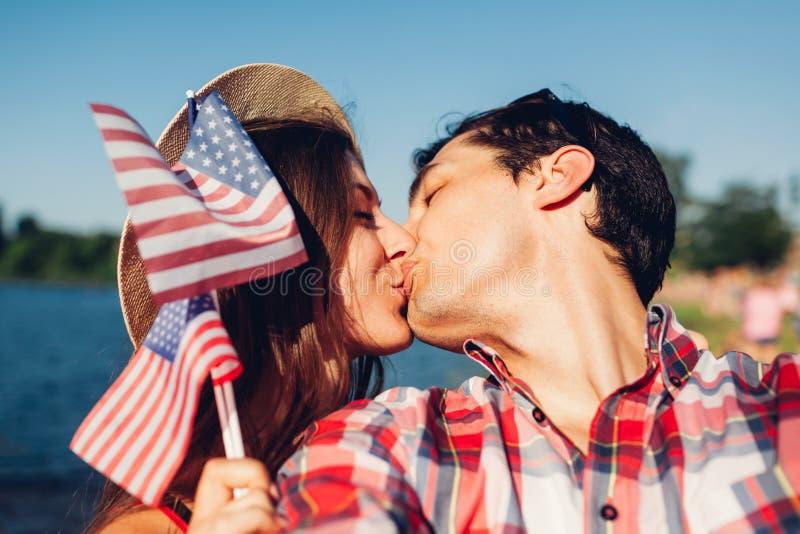 Paar in liefde die en de vlag van de V.S. kussen houden Mensen die Onafhankelijkheidsdag van Amerika vieren royalty-vrije stock afbeelding