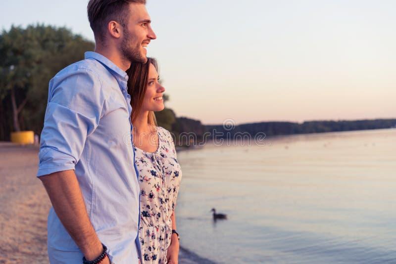 Paar in liefde die en van zonsondergang samen knuffelen genieten royalty-vrije stock fotografie