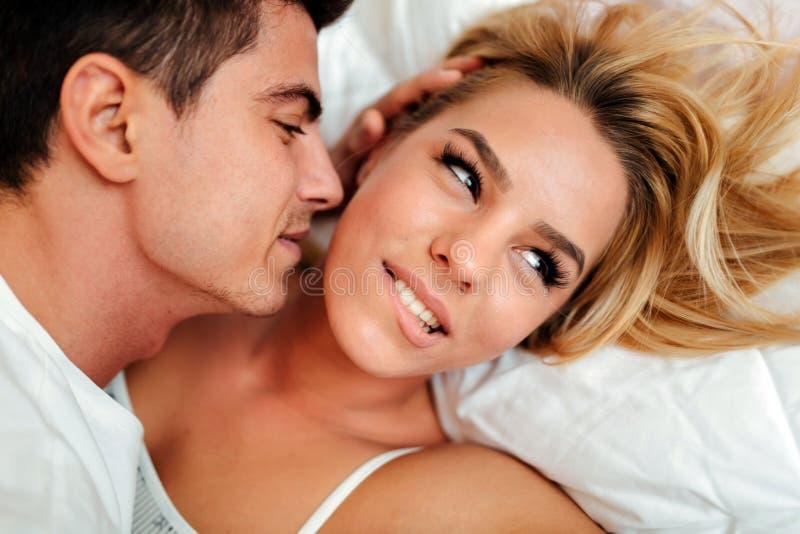 Paar in liefde die op bed liggen stock foto