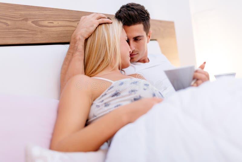 Paar in liefde die op bed liggen royalty-vrije stock fotografie