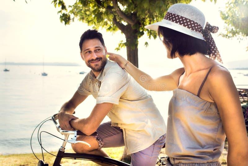 Paar in liefde die pret hebben door fiets op vakantie aan het meer royalty-vrije stock foto's