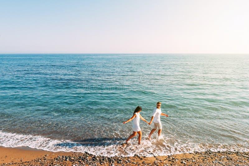 Paar in liefde die pret op het strand heeft Wittebroodswekenreis Het paar reist Man en vrouw op het strand Gelukkig Paar Looppas royalty-vrije stock foto