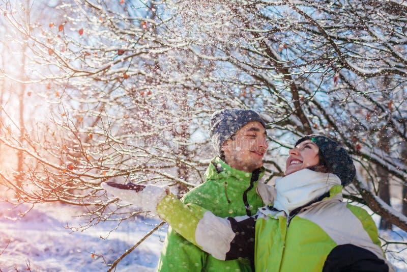 Paar in liefde die sneeuw werpen en in de winter bosjongeren koesteren die pret hebben royalty-vrije stock fotografie