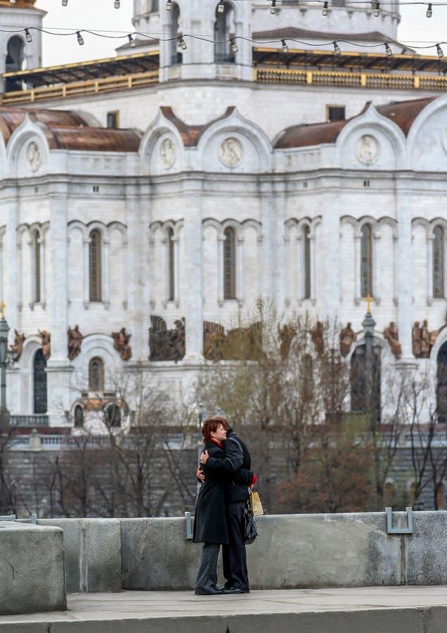 Paar in liefde die zich op de brug op achtergrond van de kerk van Moskou bevinden stock afbeelding