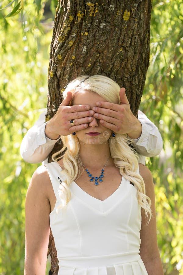 Paar in liefde Dient de man behandelde ogen van glimlachende blondevrouw door van hem park in stock foto's