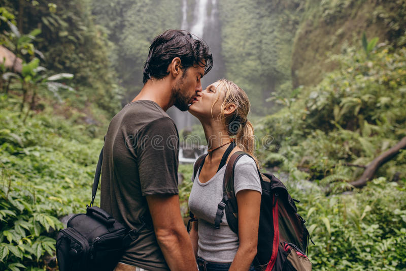 Paar in liefde het kussen dichtbij een waterval in bos royalty-vrije stock afbeeldingen