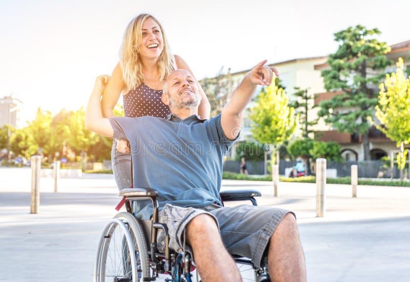 Paar in liefde in het stadscentrum man met desease op een rolstoel en zijn mooie vrouw royalty-vrije stock fotografie