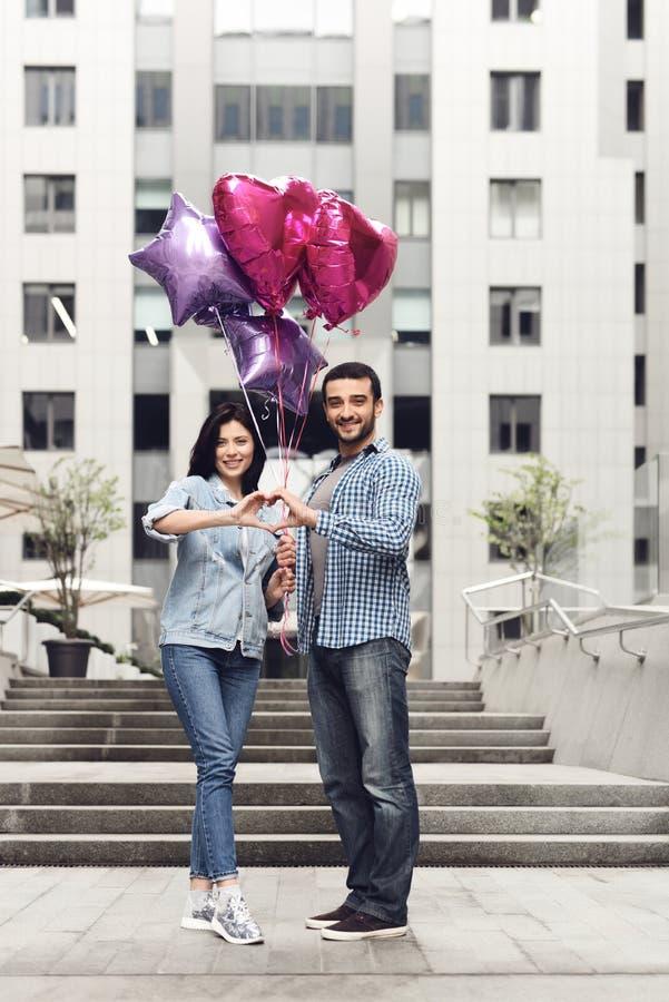 Paar in liefde met de ballons die handen samenbrengen stock afbeelding