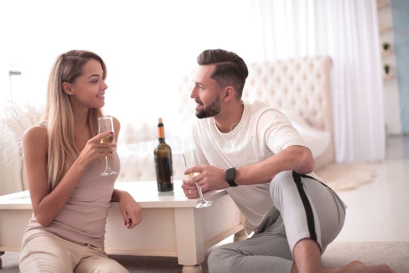 Paar in liefde met glazen van wijn het spreken zitting in de keuken royalty-vrije stock afbeeldingen