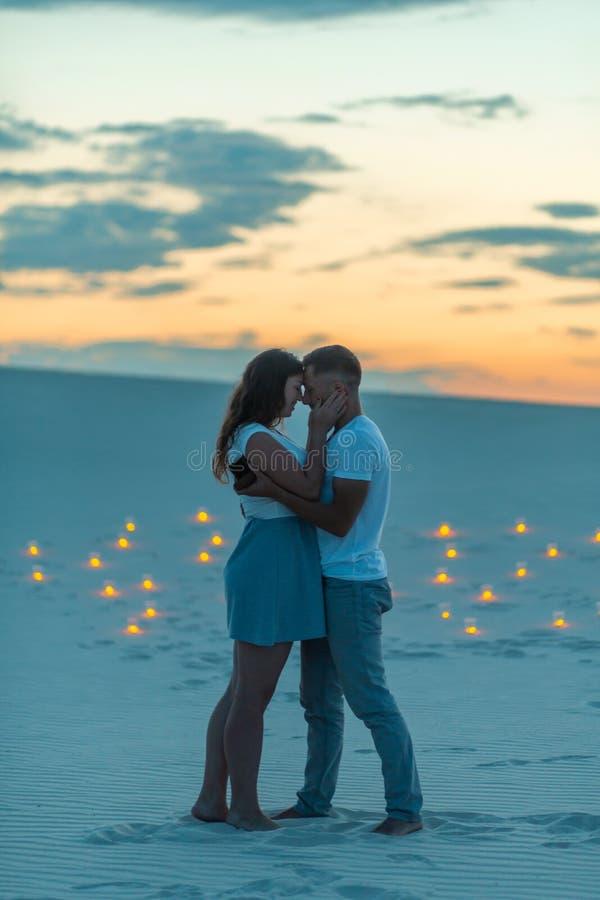 Paar in liefde romantische omhelzingen in zandwoestijn Gelijk makend, romantische atmosfeer, in de kaarsen van de zandbrandwond stock fotografie