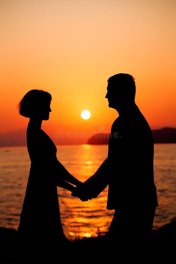 Paar in liefde Silhouet van de Mens en Vrouw tijdens Zon stock fotografie