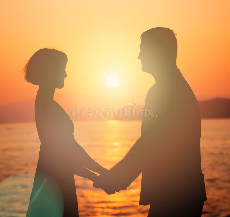 Paar in liefde Silhouet van de Mens en Vrouw tijdens Zonsondergang stock foto's