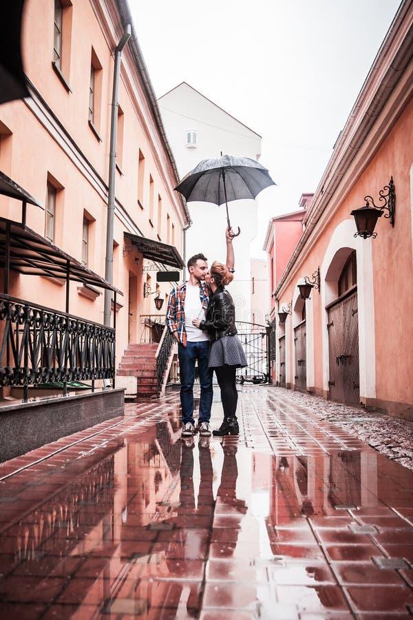 Paar in liefdekussen op de straat op een regenachtige dag royalty-vrije stock afbeelding