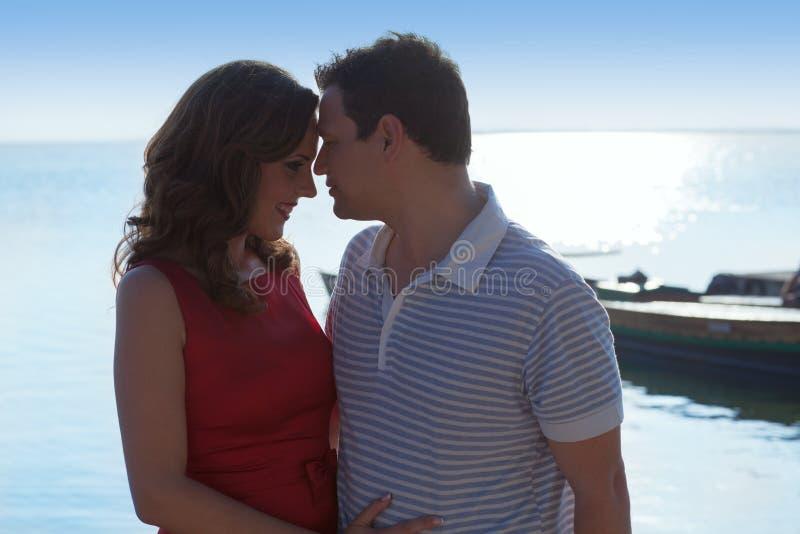 Paar in liefdeomhelzing in suset op overzees royalty-vrije stock foto