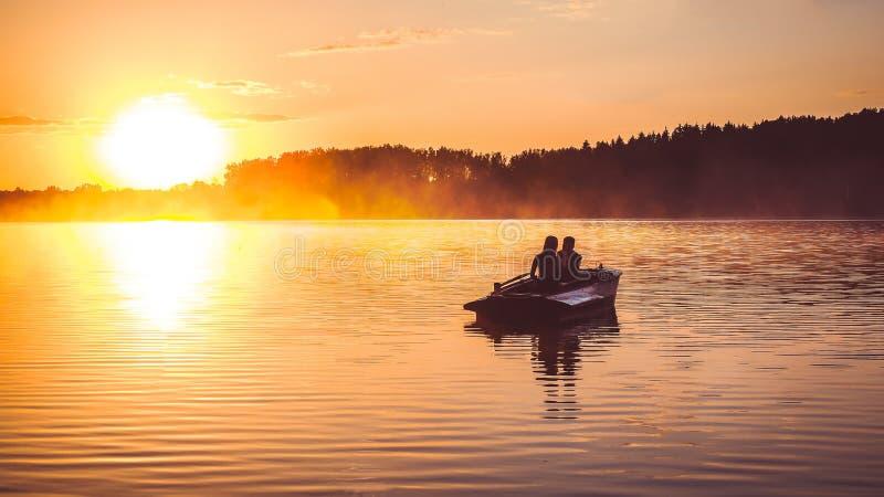 Paar in liefderit in een het roeien boot op het meer tijdens zonsondergang Romantische zonsondergang in gouden uur De gelukkige v stock foto