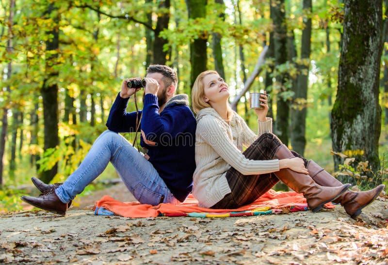 Paar in liefdetoeristen die picknickdeken ontspannen De man met verrekijkers en de vrouw met metaalmok genieten aard van park Par royalty-vrije stock afbeelding