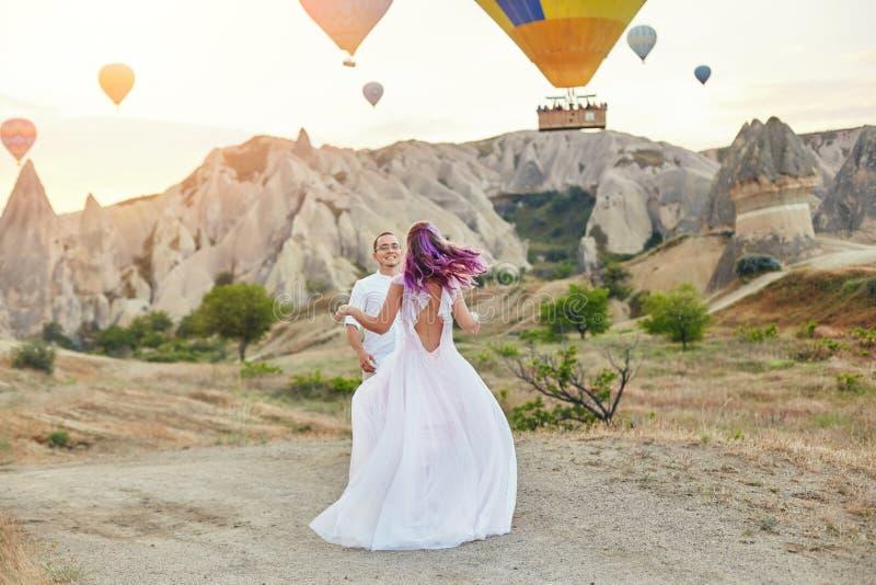 Paar in liefdetribunes op achtergrond van ballons in Cappadocia De man en een vrouw op heuvel bekijken een groot aantal vliegende stock afbeeldingen