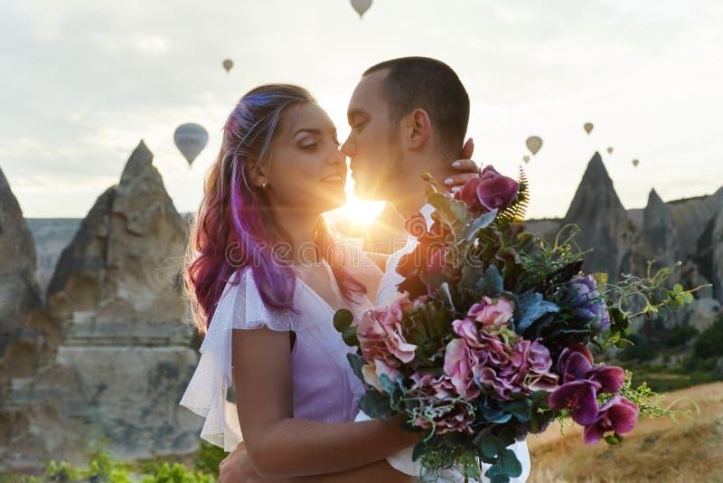 Paar in liefdetribunes op achtergrond van ballons in Cappadocia De man en een vrouw op heuvel bekijken een groot aantal vliegende stock foto's