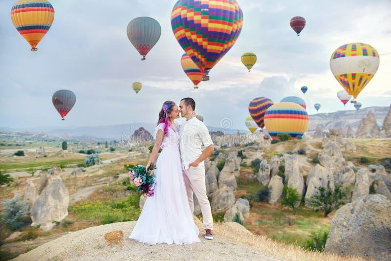 Paar in liefdetribunes op achtergrond van ballons in Cappadocia De man en een vrouw op heuvel bekijken een groot aantal vliegende royalty-vrije stock foto's