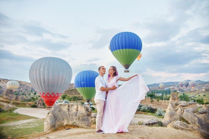 Paar in liefdetribunes op achtergrond van ballons in Cappadocia De man en een vrouw op heuvel bekijken een groot aantal vliegende royalty-vrije stock foto