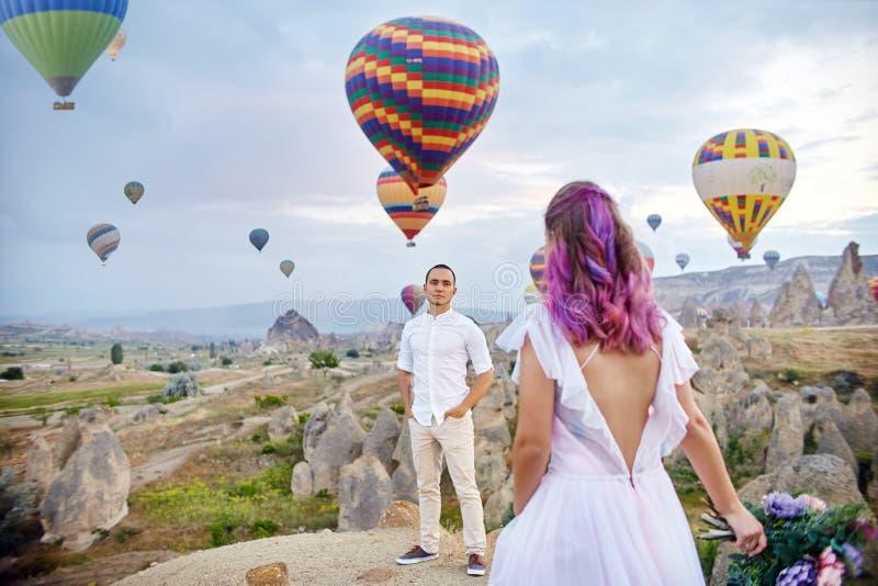 Paar in liefdetribunes op achtergrond van ballons in Cappadocia De man en een vrouw op heuvel bekijken een groot aantal vliegende stock fotografie