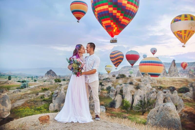 Paar in liefdetribunes op achtergrond van ballons in Cappadocia De man en een vrouw op heuvel bekijken een groot aantal vliegende stock foto